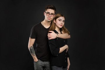 Portrait of young couple in black clothes wearing trendy glasses and posing over black background.