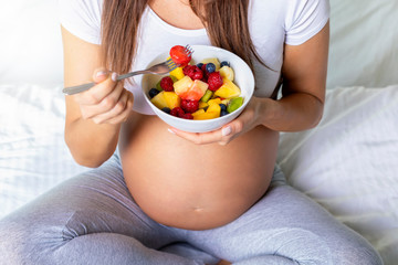 Schwangerschaft und gesunde Ernährung: schwangere Frau hält eine Schüssel mit frischem Obst in der Hand