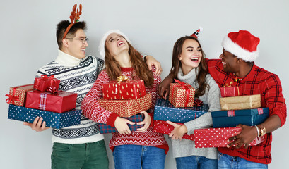 company of happy friends with Christmas gifts at empty wall.