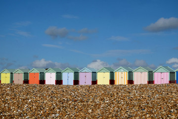 A row of ten colourful Beach huts on Brighton beach the pebble beach in the foreground and a blue sky behind