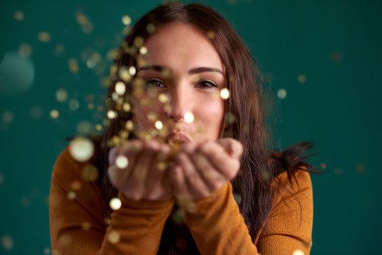 Beautiful stylish woman blowing confetti party celebration
