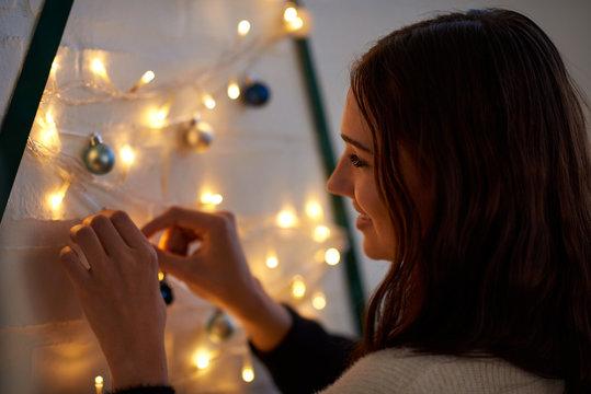 woman adjusting fairy lights on crafty christmas tree