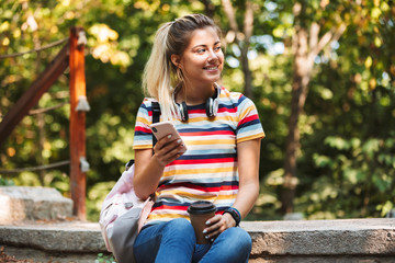 Happy cute young girl using mobile phone holding coffee.
