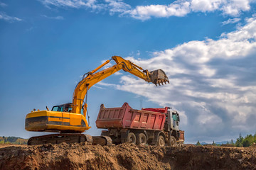 Yellow excavator and empty dump truck working at the construction site