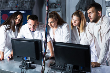 Five adults solving conundrums together in quest room in view as abandoned lab