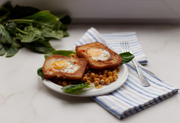Toast with egg in white plate on white marble background. Healthy breakfast