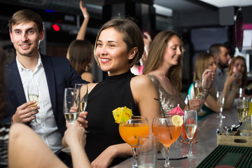 Young female is drinking cocktails with colleague