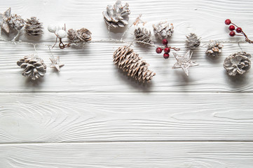 Christmas white background. Rustic garland with fir cones, red berries and snowy stars. Copy space below.