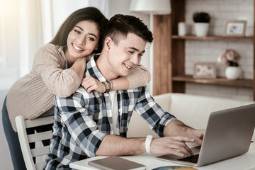 Loving couple. Delighted male person expressing positivity while working at home
