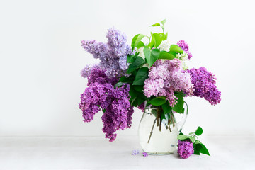 Photo sur Toile Lilac Fresh lilac flowers in glass vase over white table background
