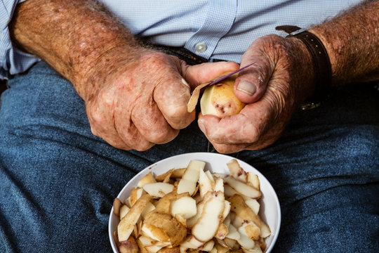 Midsection of man peeling potatoes with knife