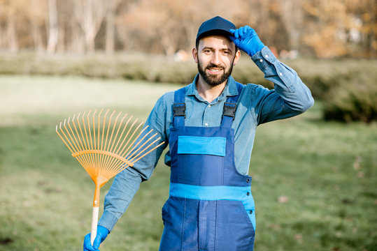 Portrait of a professional male sweeper or gardener in uniform standing with rakes in the garden