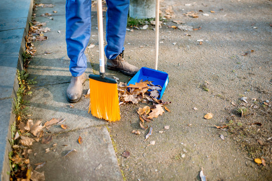 Man sweeping leaves with orange broom to the scoop on the street, close-up view with no face