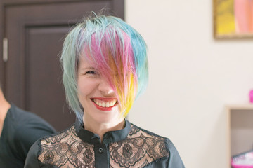 Woman 30-40 smiles and made coloring of hair in different colors in a hairdressing salon. Change the image of a woman.