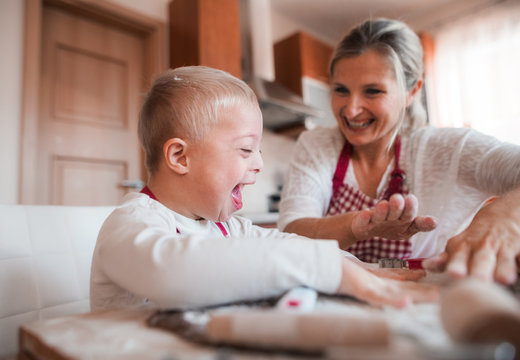 A laughing handicapped down syndrome child with his mother indoors baking.