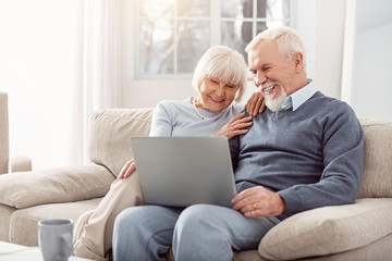 Have a look. Grey-haired cheerful woman sitting on the sofa while showing beautiful pictures to her husband