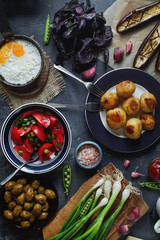 Flat lay of delicious dinner table for two with fried potatoes, organic tomatoes salad, olives, green onion, eggplants, eggs on dark stone background.
