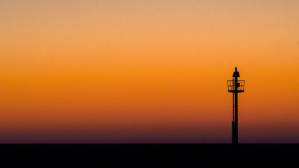 Light beacon along the harbor on a stretch dam with sunset colors.