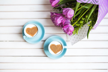 Two cups of cappuccino with a heart shaped symbol and purple tulips on a wooden background.