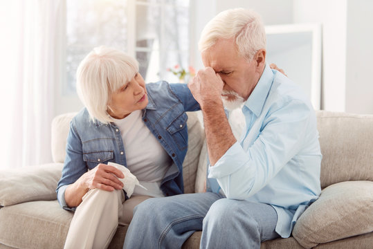 Healthcare. Short-haired aging woman looking thoughtful and worried while sitting next to her husnabd in the apartment