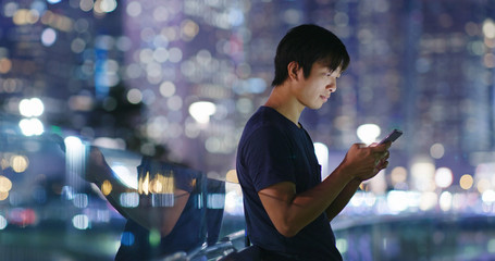 Man use of cellphone in city at night