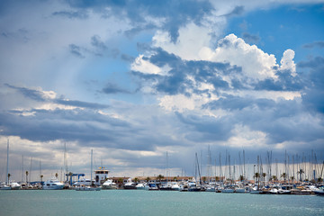 Wall Mural - Stormy clouds over marina in Port de Alcudia, Mallorca.