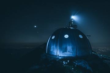 hikers shelter in the night on top of italian alps mountains - weekend activities vacation and sport concept with adventure people - dark mood filtered look