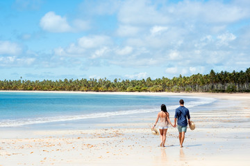 A young couple in shorts and beachwear holding hands and walking along a deserted beach