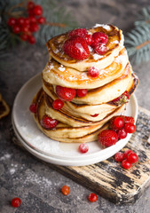 Pancakes with berry on wooden Winter Background, Christmas Dessert