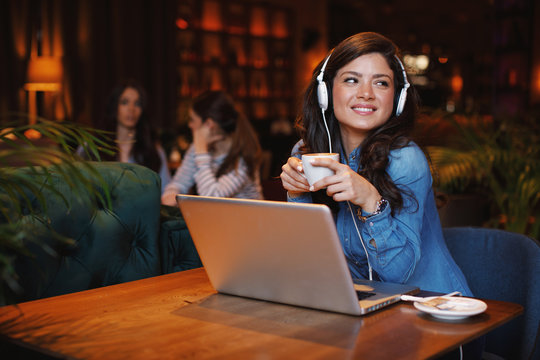 Young woman listening to music via headphones and laptom in a cafe