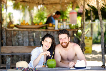 A happy young couple sharing a fresh coconut at a juice bar on a tropical beach