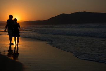 Couple in love walking on Sea sunset. Sunny path at dusk and hills on background. Georgioupolis beach, Crete Greece
