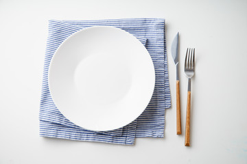 White empty plate with knife and fork on striped blue and white textile napkin on white background