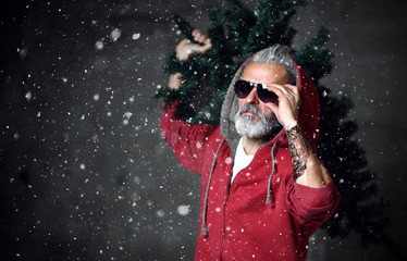 Fashionable modern Santa old man in red fashion hoodie and sunglasses Merry Christmas