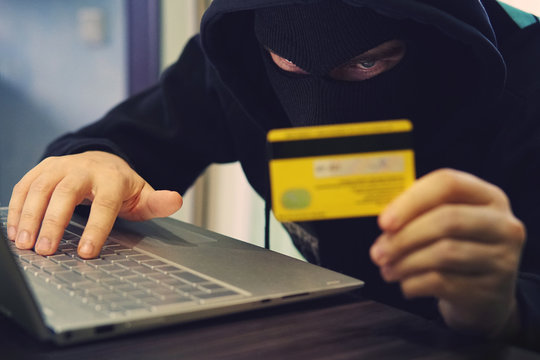 Man in robber mask uses internet, bank account and credit facilities. Phishing attack by male with hidden face. Hacker enters stolen financial data. Confidential information was taken by fraudster
