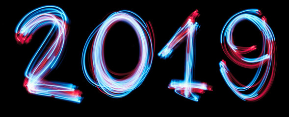 2019 happy new year number with neon lights backgrorund. blue light image, long exposure with colored fairy lights, against a black