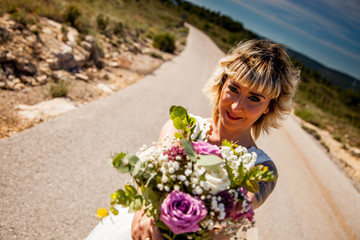 Bride poses with her bouquet on the asphalt of a lonely road