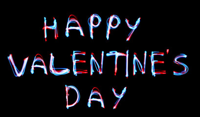 Glowing inscription happy Valentines day on a black background. blue light image, long exposure with colored fairy lights, against black