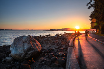 People on the Seawall along English Bay in Vancouver at Sunset. Lens Flare. British Columbia, Canada. Wall mural