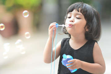 Asian little cute girl or kid blow,play air soap bubbles with smile. happiness,fun and childhood concept.