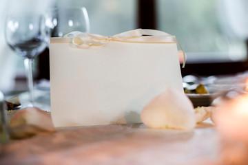 tavolo allestito elegantemente con segna posto color crema