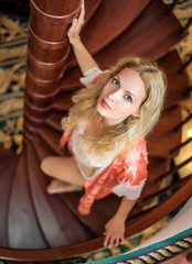 girl in silk robe stand on wooden spiral staircase
