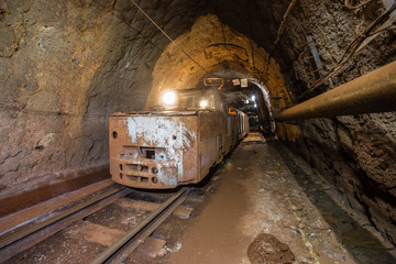 Underground gold iron ore mine shaft tunnel gallery passage with light and electric locomotive loco