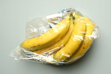 Bananas, wrapped in a plastic foil as bought in a supermarket, are seen in this picture illustration
