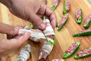 Preparation of peppers stuffed with cheese and minced meat and covered with bacon