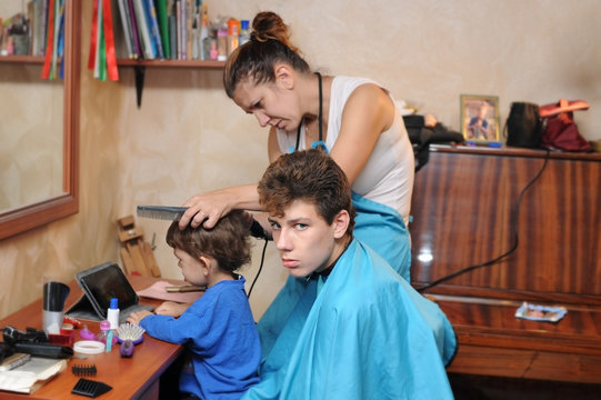 A woman works as a hairdresser at home. She cuts hair her sons with a special hairdresser's model