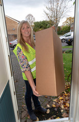 Woman courier delivering packages to a front door of a customers home