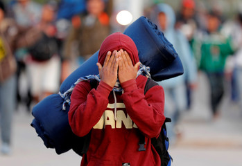 A migrant, part of a caravan of thousands traveling from Central America en route to the United States, covers his face to avoid being photographed while making their way to Tijuana from Mexicali, in Mexicali