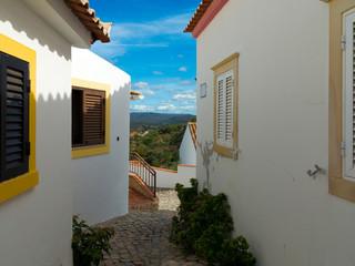 """Gasse in der Stadt """"Salir"""" an der Algarve in Portugal mit Blick auf die Berge"""