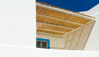 mediterranes weißes Haus mit Balkon und Sonnendach aus Schilfmatte